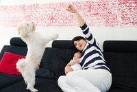 Mature woman and baby granddaughter playing with dog on sofa