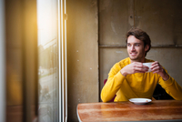 Young man sitting in cafe, drinking coffee