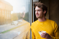 Young man sitting standing beside window, holding coffee cup