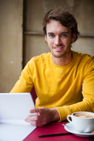 Portrait of young man in cafe, holding digital tablet