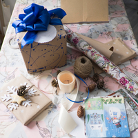 High angle view of gift wrapping and gift with blue bow on table