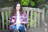 Mid adult woman reading and drinking red wine on garden bench at Thornbury Castle, South Gloucestershire, UK