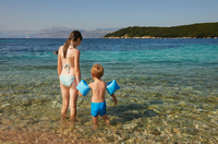 Rear view of girl and boy wearing blue armbands paddling in sea, Corfu, Greece