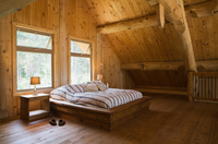 King size bed with wooden bed frame in the master bedroom, on mezzanine inside a handcrafted Eastern white pine cottage style lo