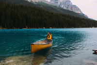 Mid adult man paddling canoe on Moraine lake, looking at camera, Banff National Park, Alberta Canada