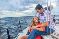 Young woman sitting between young mans legs on sailboat, face to face smiling