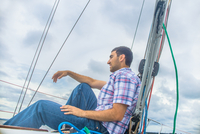 Low angle side view of young man on sailboat looking away smiling