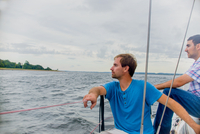 Men relaxing on sailboat looking away at view
