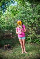 Young girl holding sunflower in front of face