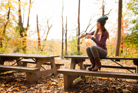 Young woman pouring drink on picnic bench in autumn forest