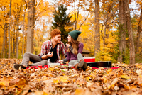 Happy young couple having picnic in autumn forest
