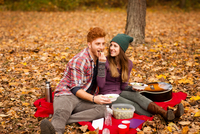 Young couple having picnic in autumn forest