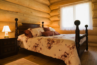 Angled view of antique wooden bed in Eastern white wood log cabin