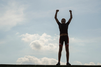 Low angle full length silhouette of mid adult man against blue sky arms raised in victory