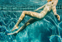 Underwater side view of nude young woman in swimming pool, arms open leaning back