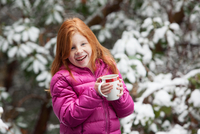 Red haired girl in front of snow covered trees, wearing pink padded coat holding mug looking away smiling