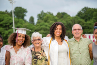 Teenage girl with mother and grandparents at graduation ceremony