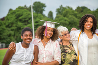 Teenage girl with sister and family at graduation ceremony