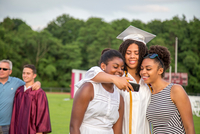 Teenage girl and sisters taking smartphone selfie at graduation ceremony