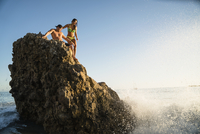 Young couple on rock with waves splashing at Newport Beach, California, USA