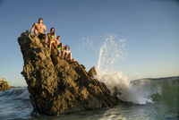 Adult friends sitting on rock formation at Newport Beach, California, USA