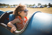 Girl sitting in barrel cart, wearing sunglasses looking away
