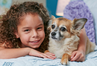 Girl lying on bed arm around dog, looking at camera smiling