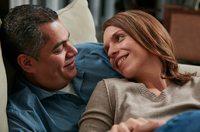 Head and shoulders of couple snuggling on sofa face to face smiling 11015270880| 写真素材・ストックフォト・画像・イラスト素材|アマナイメージズ
