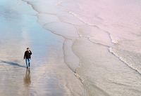 High angle front view of mature man walking on beach along coastline