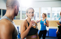 Male and female crossfitters drinking bottled water in gym