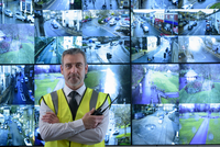 Portrait of security guard in front of in video wall in security control room