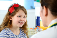 View over shoulder of girl consulting with doctor in clinic, smiling