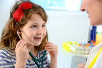 Girl listening to doctor's chest using stethoscope smiling