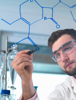 Male scientist illustrating antibiotic chemical formula in pharmaceutical research lab