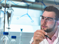Young male scientist looking at antibiotic chemical formula in pharmaceutical research lab