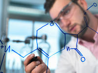 Young male scientist illustrating antibiotic chemical formula in pharmaceutical research lab