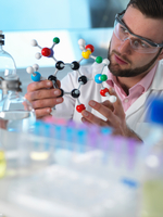 Scientist examining molecular model structure in laboratory