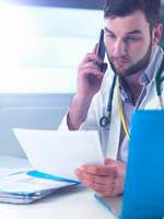 Junior doctor using smartphone whilst reading medical records in clinic