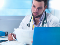 Junior doctor reading medical records in clinic