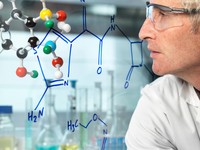 Scientist with ball and stick molecular model looking at new drug formula written on glass