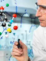 Scientist with ball and stick molecular model writing formula of new drug on glass