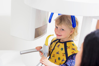 High angle view of girl in x-ray machine having dental examination smiling