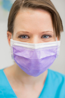 Portrait of young female dentist wearing mask looking at camera