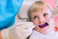 Girl with plaque disclosing tablet on teeth having dental examination