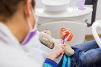 Cropped view of boy in dentist chair holding teddy bear brushing dentures