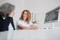 Surface level view of mature woman and senior woman discussing x-ray image on computer screen