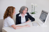 Senior woman and mature woman at desk discussing x-ray image on computer screen smiling