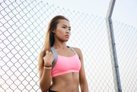 Young woman wearing crop top by wire fence