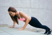 Young woman exercising doing push ups on city stairway