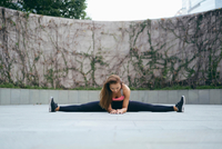 Young woman outdoor exercising doing the splits